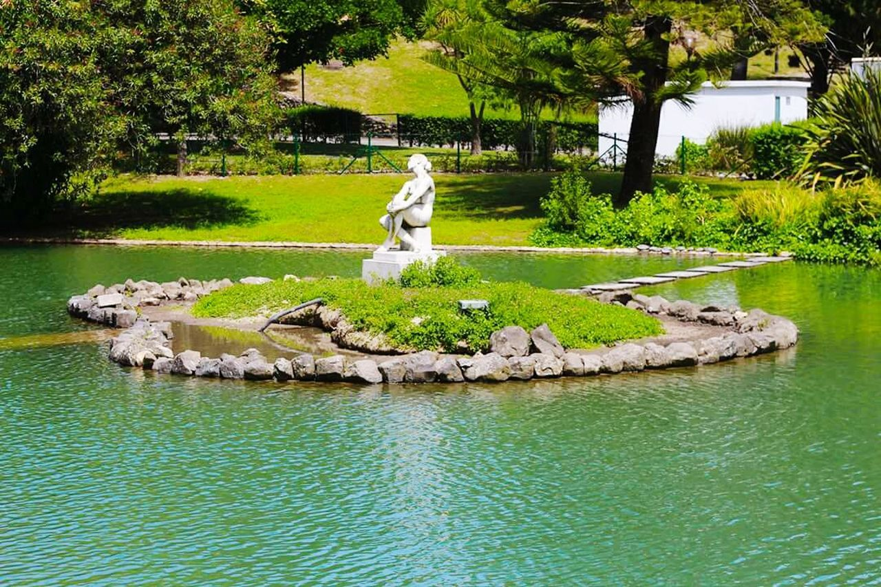 statue, human representation, tree, sculpture, male likeness, art and craft, water, day, rock - object, outdoors, nature, tranquil scene, park - man made space, no people, grass, full length, beauty in nature