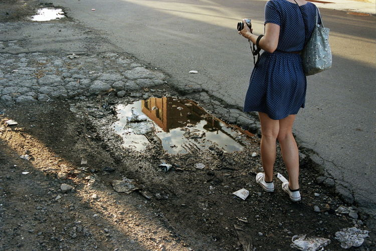 Low Section Of Woman Holding Camera While Standing By Puddle On Street