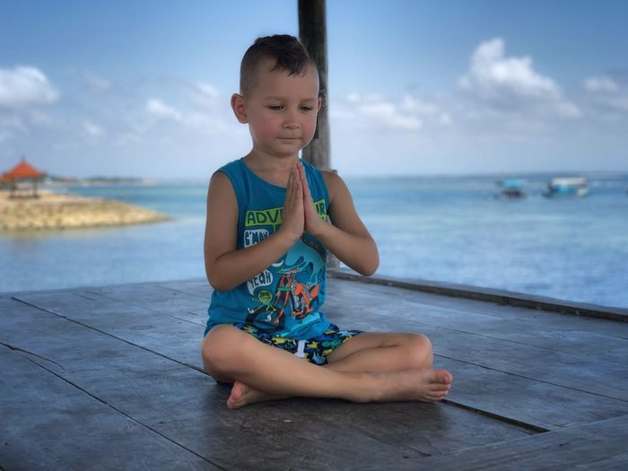 Boy praying while sitting on wooden floor by sea