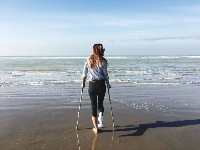 Full length of disabled woman with walking canes standing at beach against sky