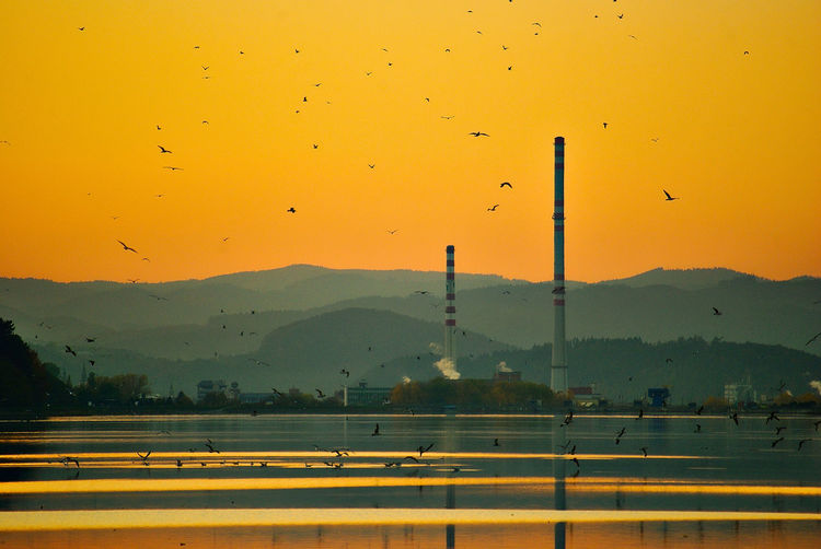 Air Pollution Animal Animal Themes Architecture Beauty In Nature Bird Environment Factory Fuel And Power Generation Industry Landscape Mountain Nature No People Orange Color Outdoors Pollution Scenics - Nature Sky Sunset Vertebrate Yellow