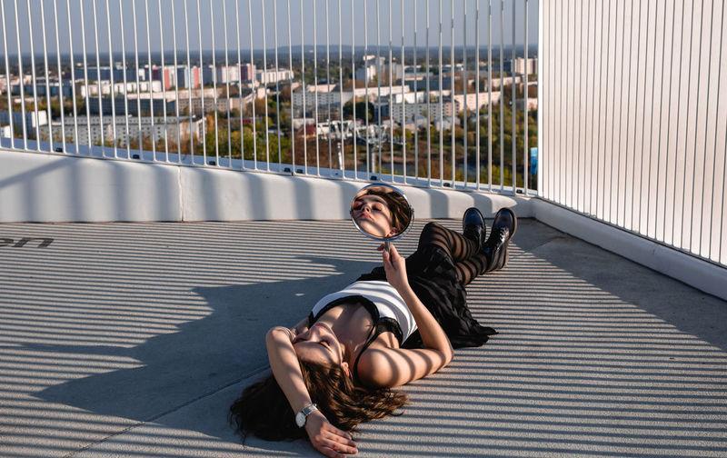 Young woman lying down on railing