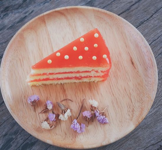Close-Up Of Cake Slice With Flowers In Wooden Plate On Table