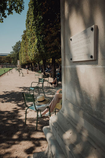 Empty chairs and table against trees in city