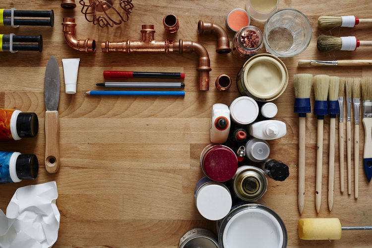 Directly above shot of work tools and plumbing equipment on wooden table