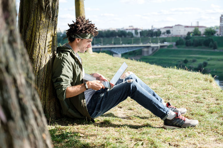 Man using laptop while sitting by tree trunk