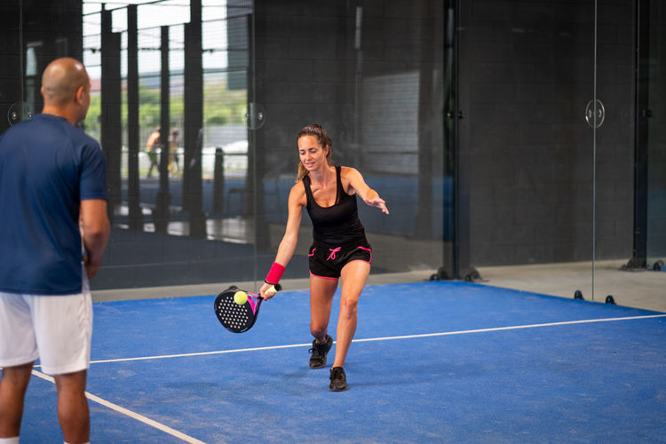 Monitor teaching padel class to woman, his student - trainer teaches young girl how to play padel