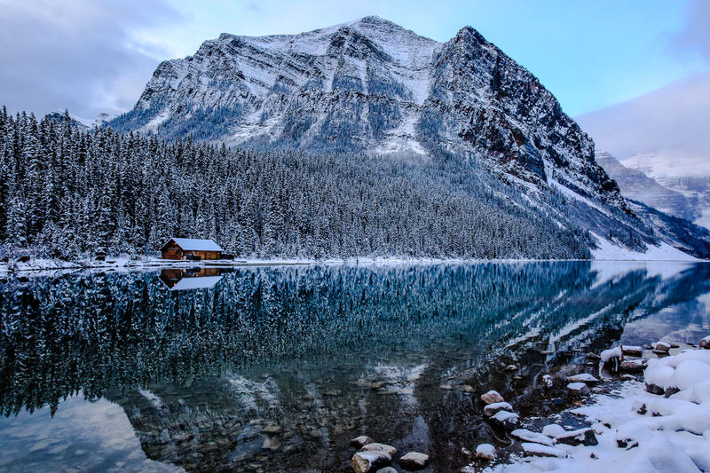 Canadian rockies in October, mountain range dusted in first snow, cloudy, morning light. small wooden hut on the other side of the lake. Reflection on th ewater in the foreground Mountain Cold Temperature Snow Winter Scenics - Nature Beauty In Nature Water Mountain Range Sky Nature Tranquil Scene Lake Non-urban Scene Cloud - Sky Day Tranquility No People Idyllic Snowcapped Mountain Outdoors Ice Formation Mountain Peak Lake Louise,Alberta Banff National Park  EyeEmNewHere