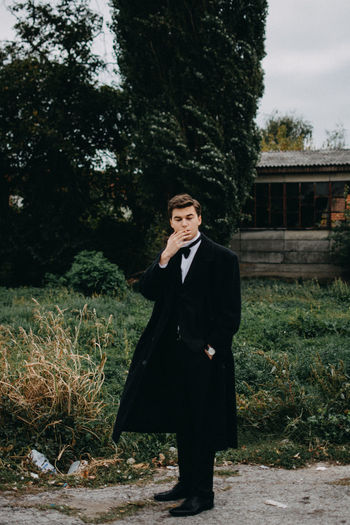 Young Man smoking a cigarette Fashion Man Smoke Smoking Well Dressed Adult Contemplation Day Formalwear Front View Full Length Lifestyles Looking Nature One Person Outdoors Plant Portrait Real People Standing Suit Tree Well-dressed Women Young Adult