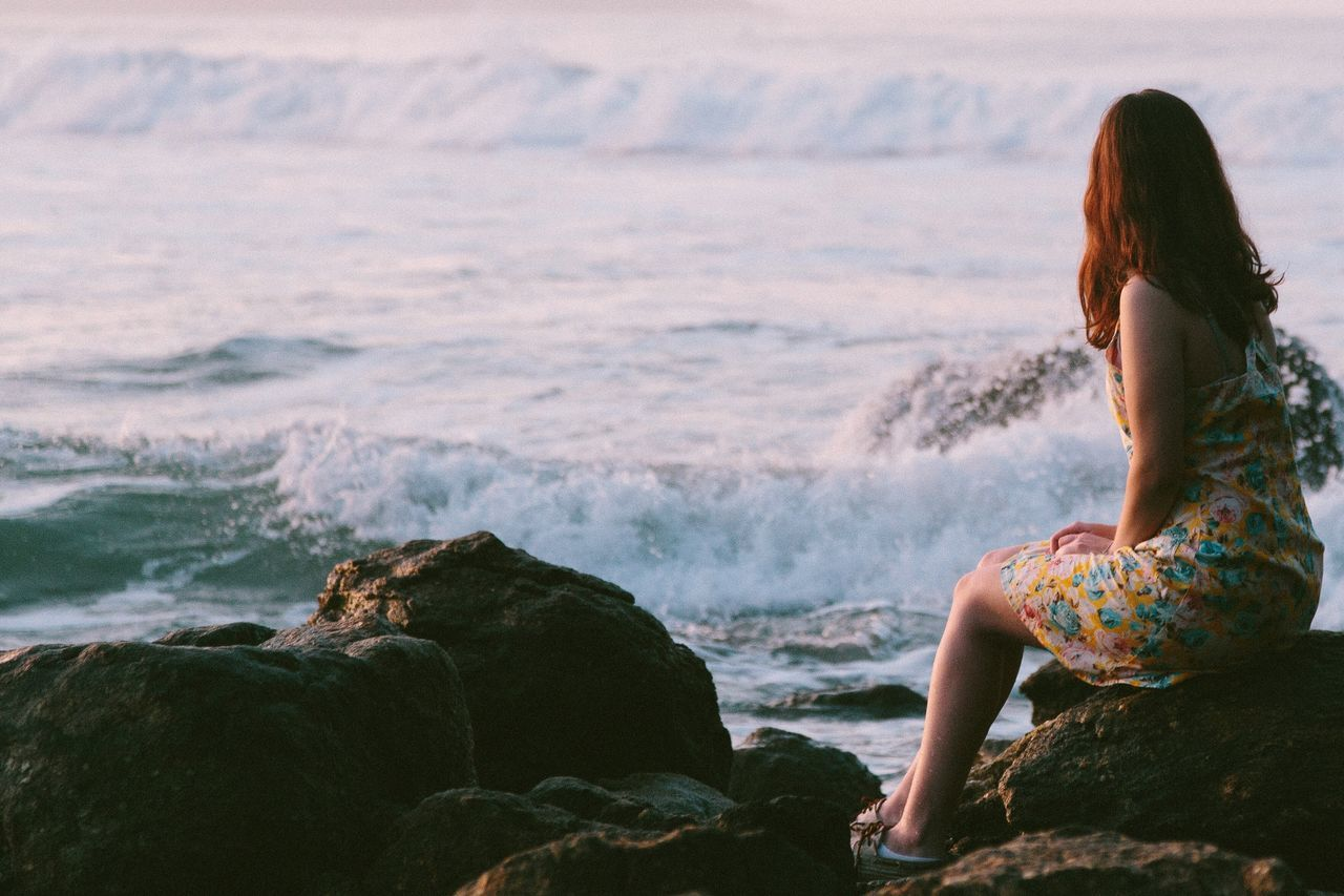 Woman wearing dress sitting on rock against sea