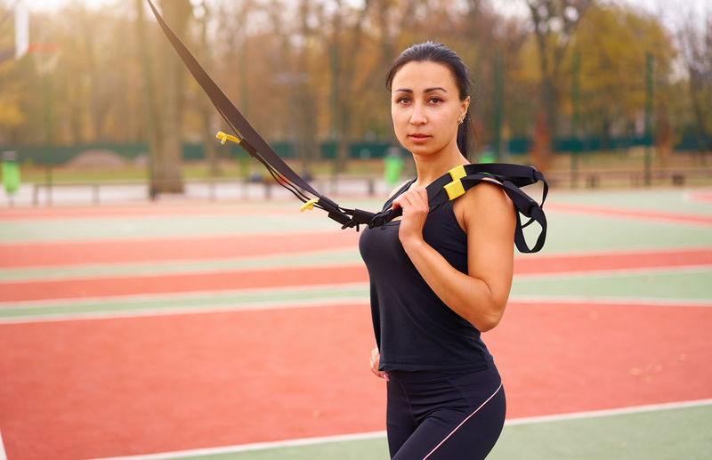 Portrait of smiling woman exercising with equipment at court