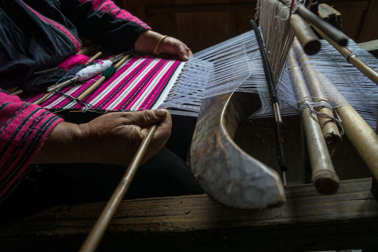 Low section of man working on loom