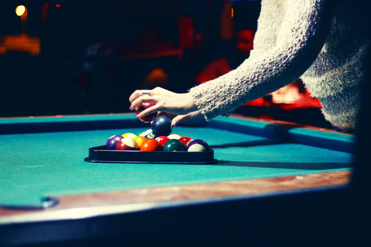 Midsection Of Woman Arranging Pool Balls