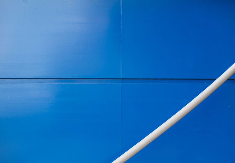 White Metallic Pipe Against Blue Wall