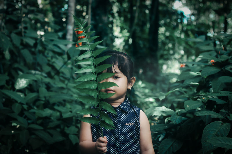 Boy standing by plants in forest