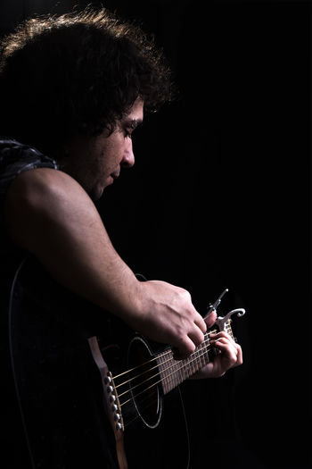 Side view of man playing guitar against black background
