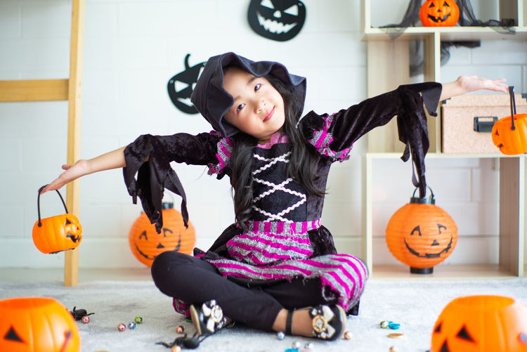 Full length of a girl sitting on a halloween