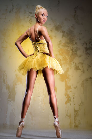 Portrait of beautiful ballerina tiptoeing against yellow background