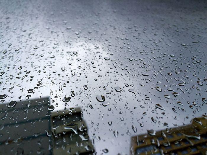 High Angle View Of Rain Drops On Glass
