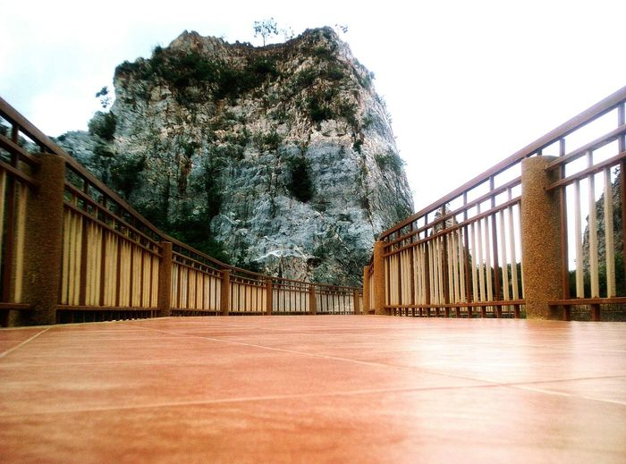 Empty footbridge against rock formation