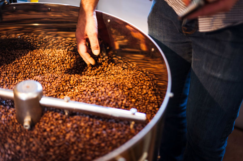 Cropped image of man grinding coffee beans on espresso maker at cafe