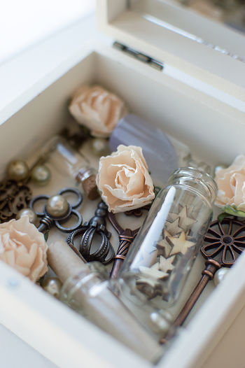 High angle view of old keys and decorations in box on table