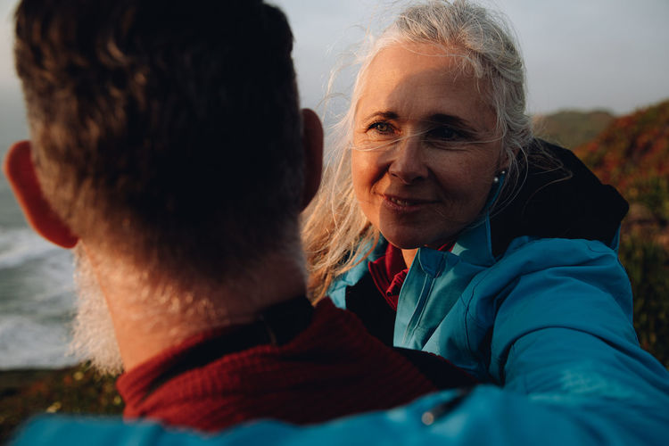 Close-up of smiling mature woman talking with man at beach