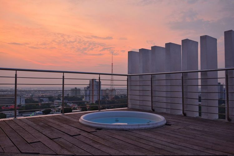 Modern buildings by swimming pool against sky during sunset