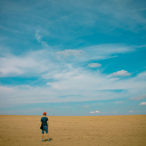 Rear View Of Boy Standing On Field Against Sky