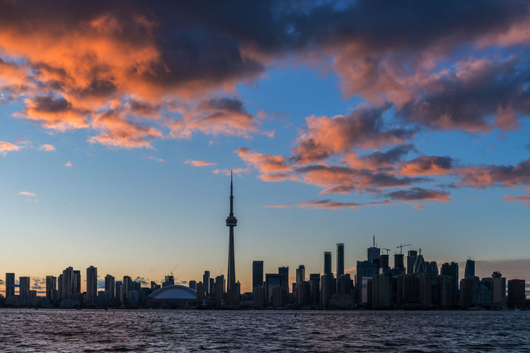 View of city skyline against cloudy sky during sunset