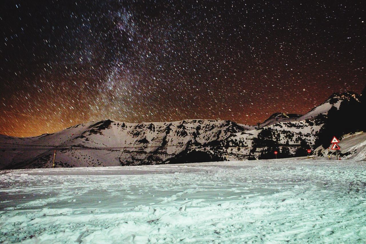 SCENIC VIEW OF SNOW COVERED MOUNTAINS AT NIGHT