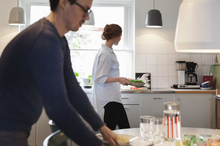 Man and woman standing in front of people at home