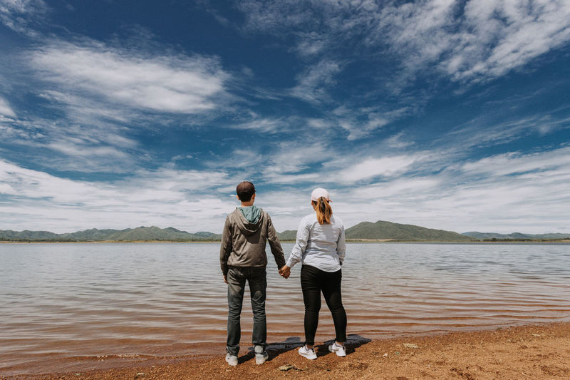 Rear view of couple holding hands while standing at beach