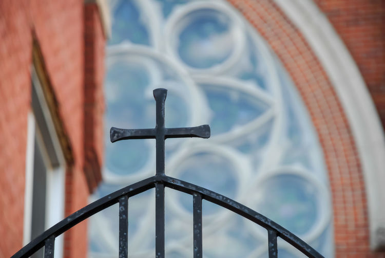 Low angle view of cross on railing against building