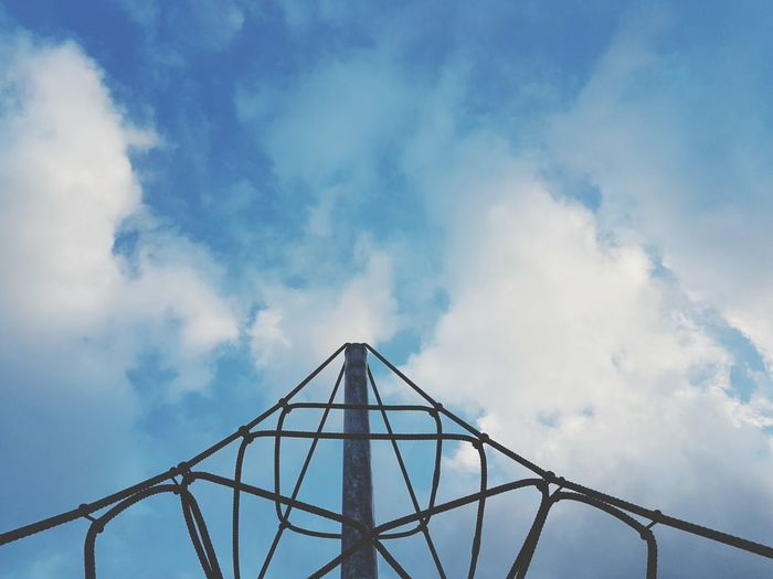 Low angle view of jungle gym at playground against blue sky