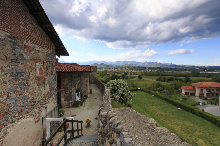 Candelo, Biella - May 4, 2016: View form the inside of the Medieval village of Ricetto di Candelo in Piedmont, used as a refuge in times of attack during the Middle Age. Architecture Biella Building Exterior Built Structure Candelo Candelo In Fiore Cloud Cloud - Sky Cloudy Day Grass House Italy Landscape Medieval Village Mountain Nature No People Outdoors Residential Building Residential Structure Ricetto Di Candelo  Rural Scene Sky Village