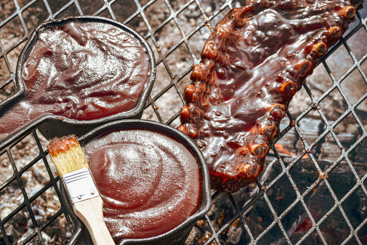 Baby back pork ribs and cast iron pots  full of barbecue sauce on grill