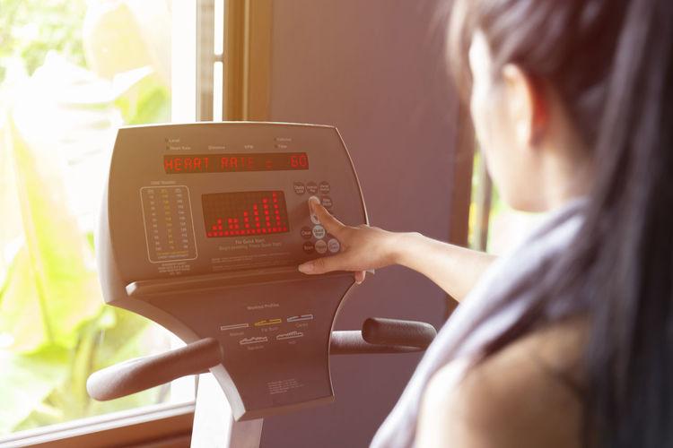 Woman using treadmill in gym
