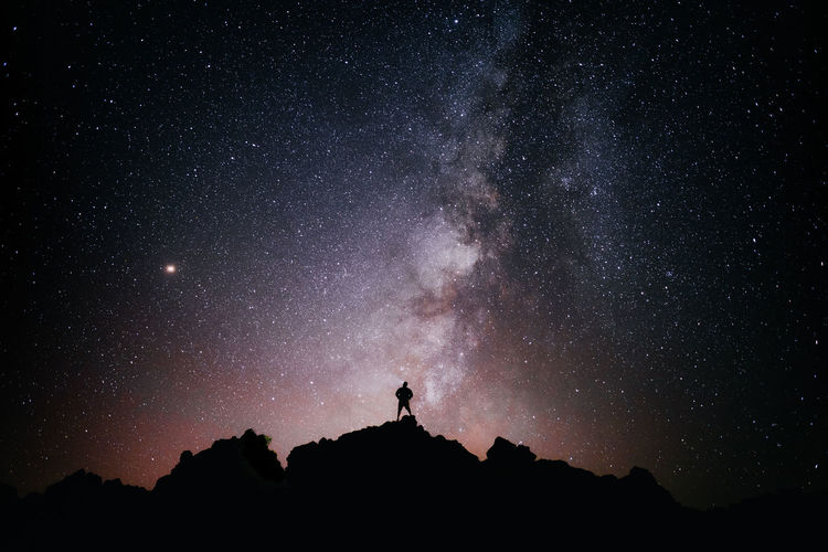 Silhouette man standing against star field at night