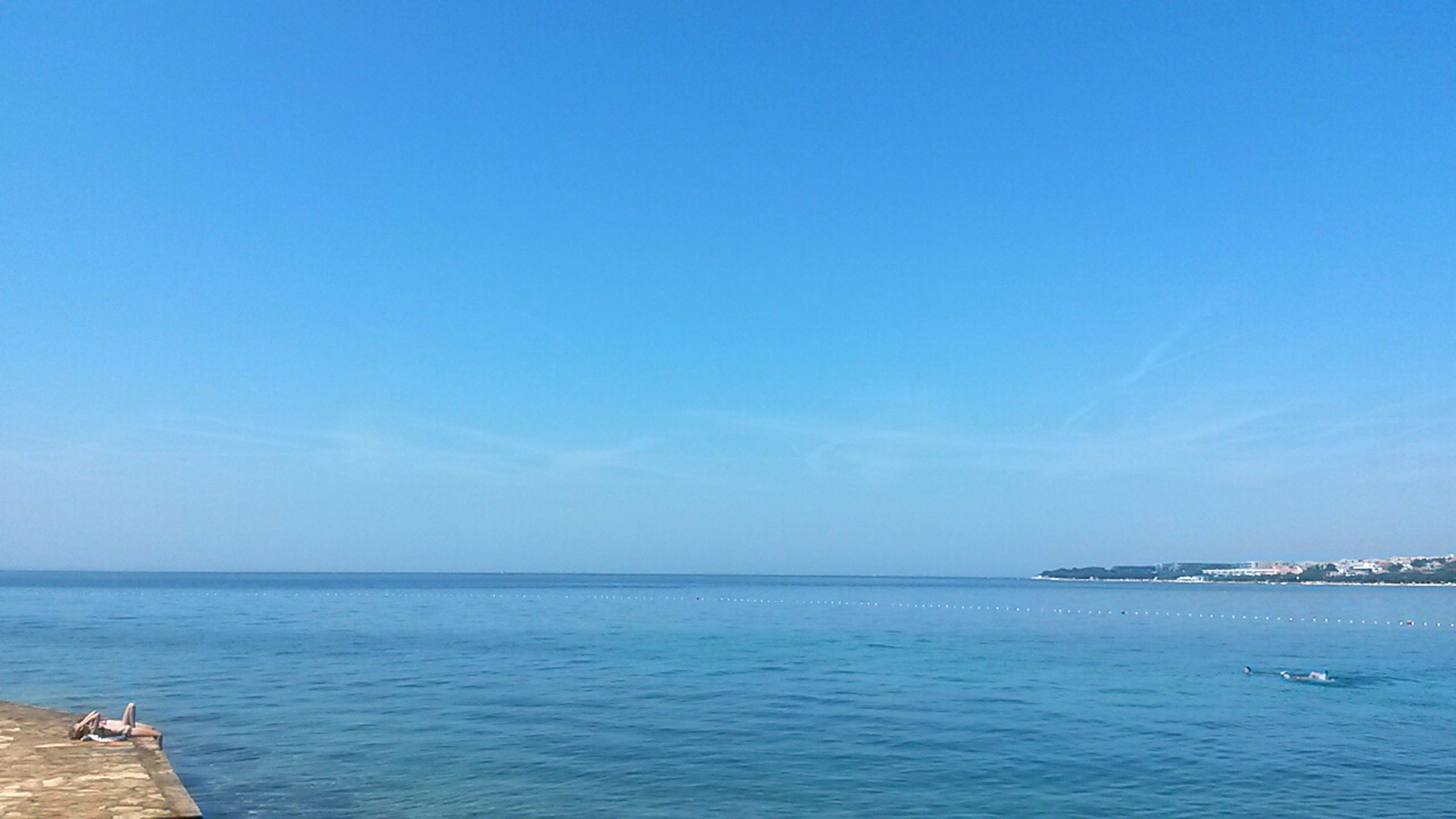 sea, water, blue, horizon over water, copy space, tranquil scene, tranquility, scenics, beauty in nature, clear sky, nature, sky, waterfront, idyllic, beach, seascape, outdoors, day, calm, nautical vessel