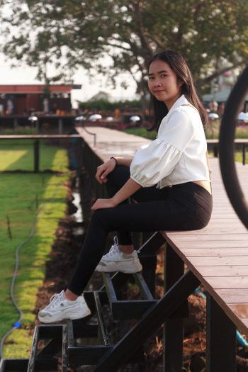 Portrait of woman sitting on railing