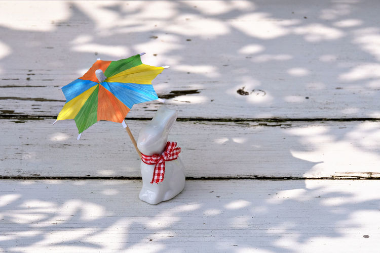 Animal Themes Beauty In Nature Easter Figurine  Happy Easter Isolated Color Multi Colored Multicolored Sunshade Multicolored Umbrella No People Old Bench Outdoors Porcelain Rabbit Rabbit Rabbit Figurine Red Ribbon Reflections Sunprotection Sunshade Sunshine Umbrella White Bench Paint The Town Yellow