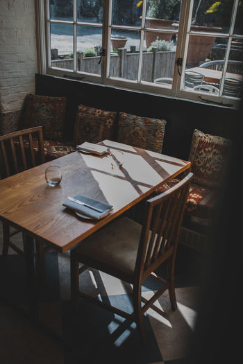Absence Arrangement Business Chair Day Dining Table Empty Flooring Food And Drink Furniture Glass Glass - Material Indoors  No People Restaurant Seat Setting Still Life Table Window Wood - Material