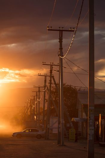 Electricity pylon by road against dramatic sky during sunset