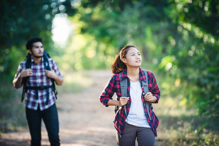 Thoughtful Male And Female Hikers Carrying Backpacks In Forest