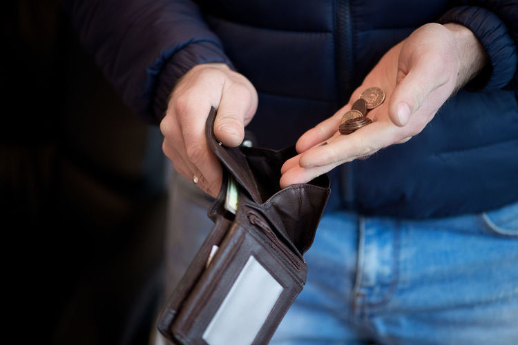 Midsection of man putting coins in wallet