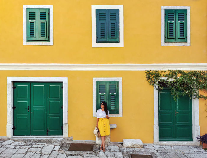 Young woman in summer outfit standing in front of yellow house.