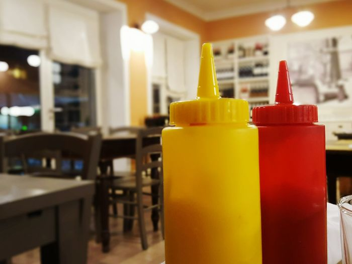 Close-up of red and yellow bottle on table at illuminated restaurant
