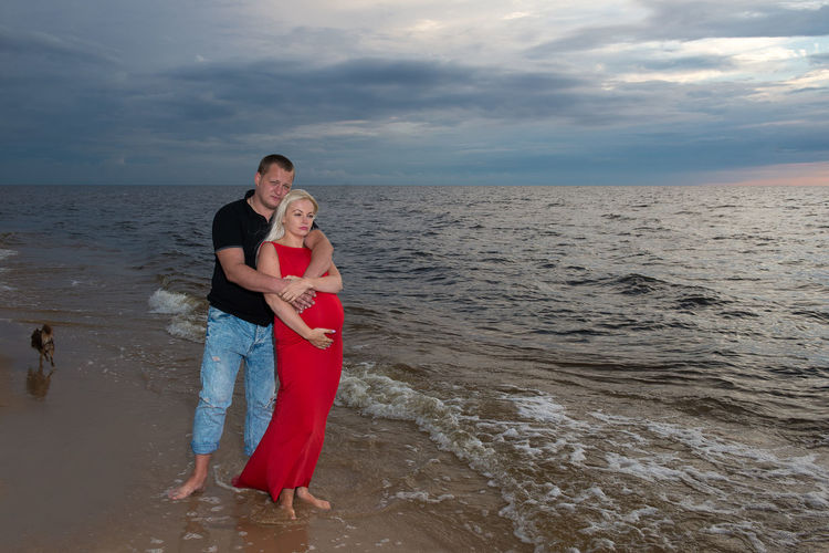 Pregnant couple standing at beach against sky during sunset
