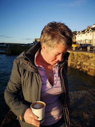 woman looking down at the ground with a coffee in her hand Woman Looking Down Porthleven Eyeemphotography One Person Lady Woman With Shorthair Blue Sky Outdoors Water Drink Beach Clear Sky Warm Clothing Drinking Sky Close-up Cappuccino Ocean Coffee Cup
